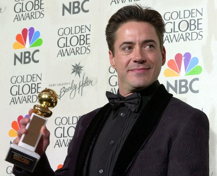 Actor Robert Downey Jr., poses with his award afte