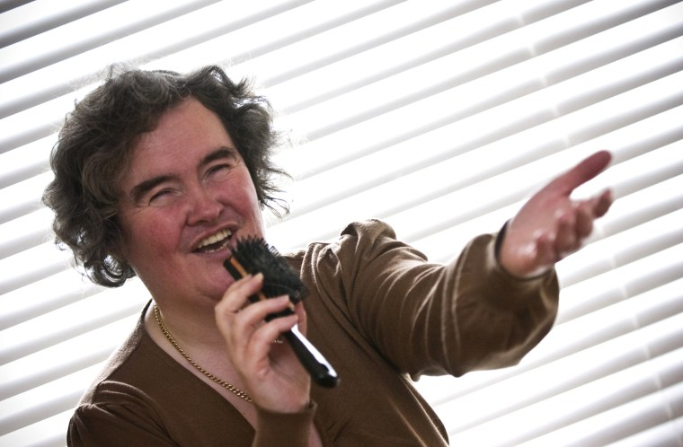 "Susan Boyle, who's performance on the television show ""Britain's Got Talent"" wowed the judges, poses singing with a hairbrush at her home in Blackburn, Scotland, Thursday April 16, 2009. The frumpy 47-year-old, who says she's never been kissed, has gained celebrity fans and millions of admirers - including a fair number of men - since appearing on the show. Her fame has been fueled by new technology, with a clip of her performance viewed more than 12 million times on YouTube.(AP Photo)"
