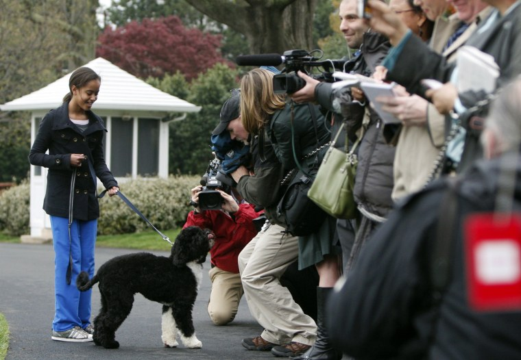 U.S. President Barack Obama's daughter Malia takes her dog Bo for a walk on the South Lawn at the White House in Washington