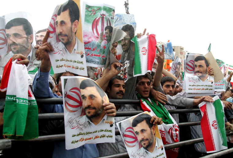 Thousands of supporters of Iran's hardline President Mahmoud Ahmadinejad (portraits) wave national flags during a massive rally to celebrate his victory in the presidential elections in Tehran's Valiasr square on June 14, 2009. Ahmadinejad defended his June 12 re-election but his defeated rival, Mir Hossein Mousavi, demanded the result be scrapped, setting the stage for further tense confrontations after the authorities cracked down on opposition protests. AFP PHOTO/ATTA KENARE (Photo credit should read ATTA KENARE/AFP/Getty Images)