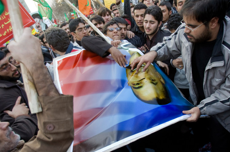 Students tear up a picture of U.S. President-elect Obama during anti-Israel and anti-U.S. rally in Tehran