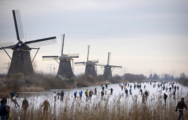 People skate on frozen canals in Kinderdijk's Mill Area, a UNESCO World Heritage site, near Rotterdam, Netherlands, Saturday Jan. 3, 2009. Kinderdijk, where the mills date back to the 18th century, is a good example of a low countries area where water management is carefully organised with a system of historic mills and waterways. (AP Photo/Peter Dejong)