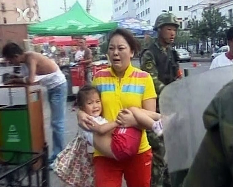 Image: Video grab from Xinjiang TV shows a crying woman carrying baby next to a soldier in Urumqi