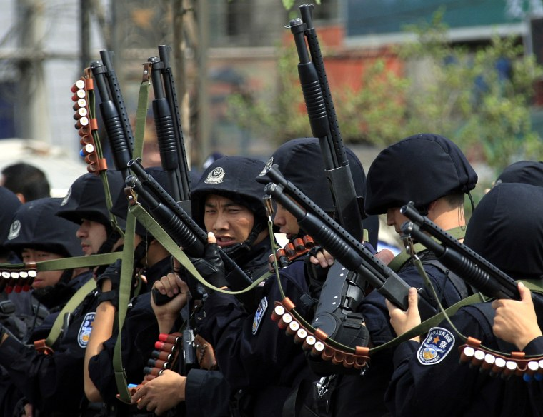 Image: Armed Chinese policemen march towards a group of local women during a confrontation along a street in the city of Urumqi