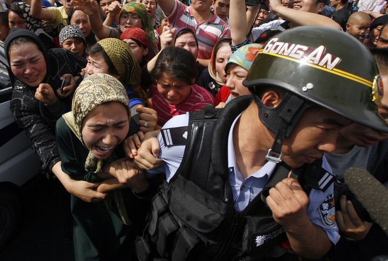 Image: A woman holds onto a Chinese policeman as a crowd of locals confront security forces along a street in the city of Urumqi