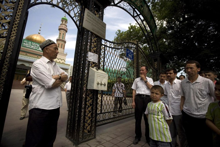 Image: Ethnic Uygurs stand outside a closed mosque minutes before Friday prayer in Urumqi, China