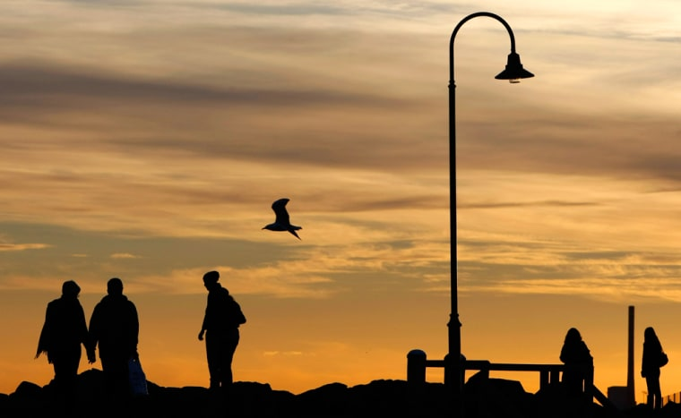 Image: People walk along a pier on St Kilda beach in Melbourne.