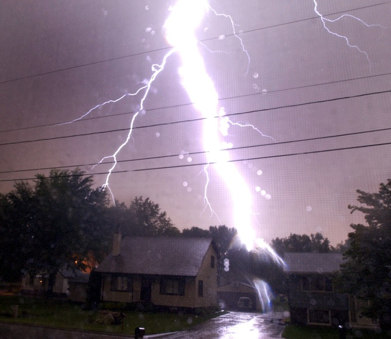 Lightning strikes as seen behind a house north of Center Street NE in Cedar Rapids. A severe storm passed through the Cedar Rapids metro area Thursday night Aug. 26, 2004.