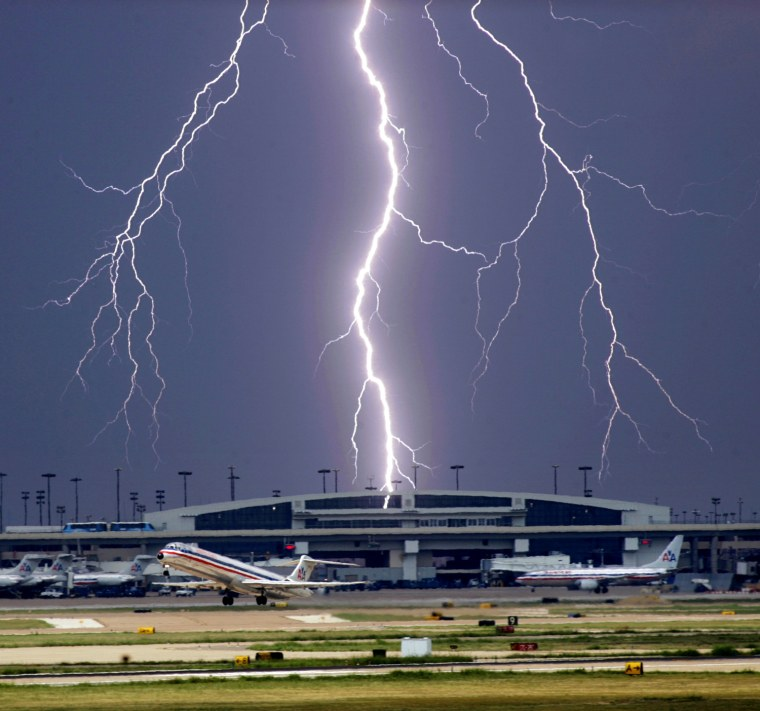 A bolt of lightning strikes near Terminal D as an American Airlines jet takes off from Dallas/Fort Worth International Airport, Monday, Sept. 11, 2006, near Dallas, before an approaching storm moves through the area. (AP Photo/The Dallas Morning News, Tom Fox) ** MANDATORY CREDIT: NO SALES, MAGS OUT, TV OUT, INTERNET: AP MEMBERS ONLY **