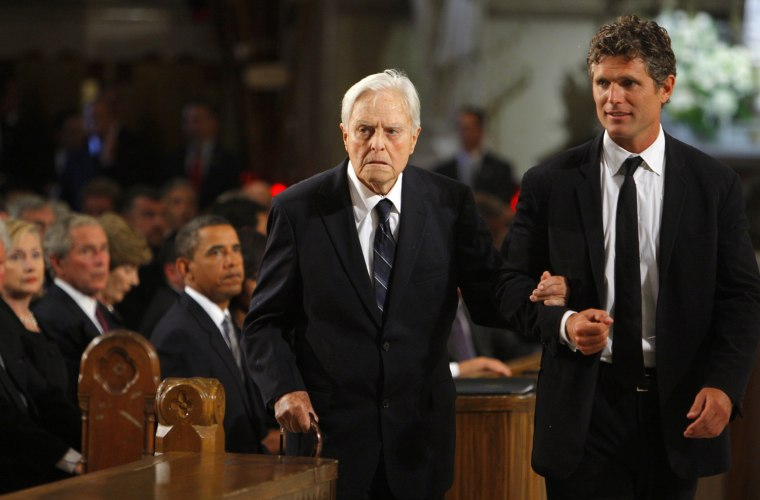 Image: Senator Edward Kennedy's brother in law Sargent Shriver is escorted to his seat in the church by his son Anthony Kennedy Shriver as U.S. President Barack Obama , former President George W. Bush and Secretary of State Hillary Clinton look on during