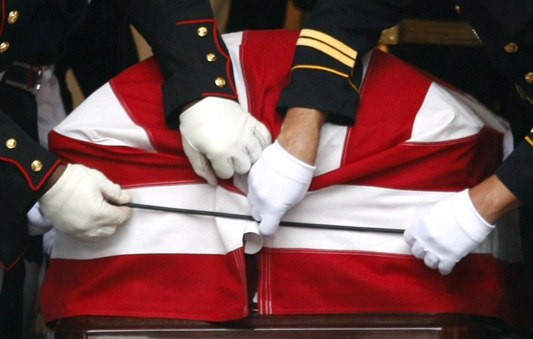 Image: Members of military pallbearers fasten U.S. flag to coffin of U.S Senator Kennedy before it is carried out of Basilica of Our Lady of Perpetual Help