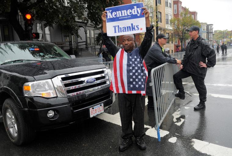 Image: Christopher Nzewwa, a native of Nigeria and longtime Boston resident, holds a sign thanking Senator Edward Kennedy