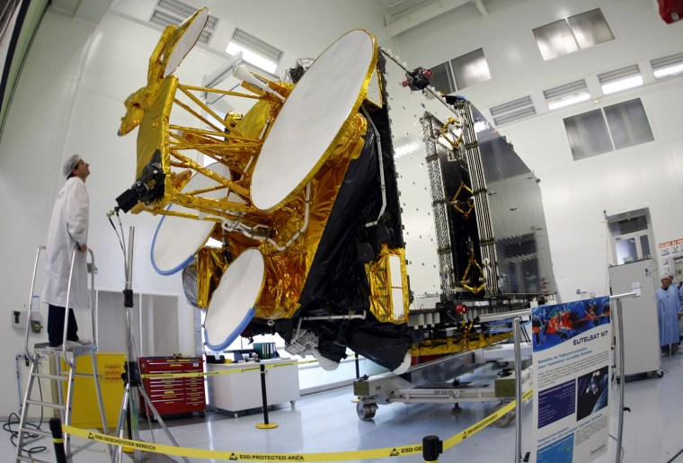 Image: A technician checks the Eutelsat's W7 communications satellite during a press visit at Thales Alenia Space in Cannes