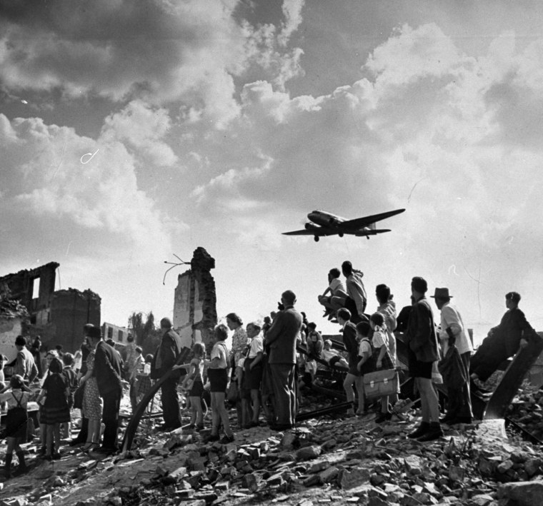 US C-47 cargo plane flying over locals amid ruins,