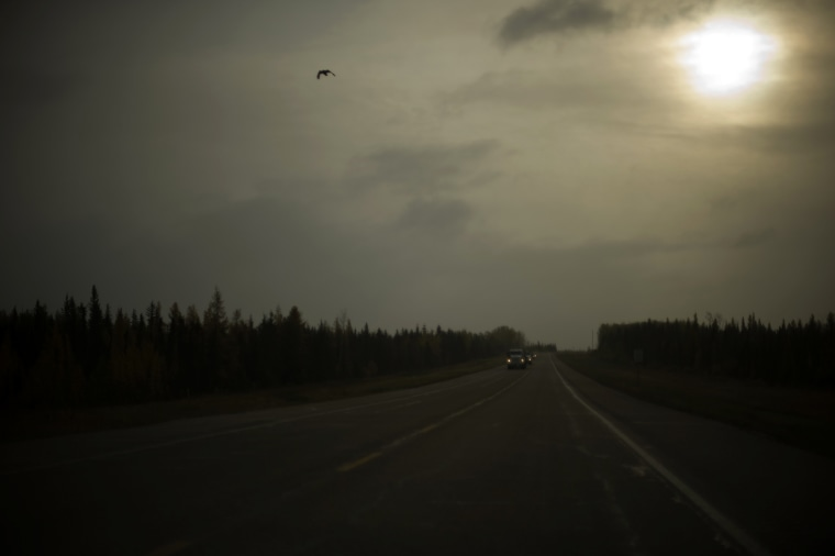 The road leading to the Fort McMurray Airport.   The Oil Sands or Tar Sands region in Alberta, Canada is now one of the largest producers of petroleum in the world. The Athabasca Oil Sands (also known colloquially as the Athabasca Tar Sands although there is no actual tar) are large deposits of bitumen, or extremely heavy crude oil, located in northeastern Alberta, Canada - roughly centered around the boomtown of Fort McMurray. These oil sands, hosted in the McMurray Formation, consist of a mixture of crude bitumen (a semi-solid form of crude oil), silica sand, clay minerals, and water. The Athabasca deposit is the largest reservoir of crude bitumen in the world and the largest of three major oil sands deposits in Alberta, along with the nearby Peace River and Cold Lake deposits. Together, these oil sand deposits lie under 141,000 square kilometres (54,000 sq mi) of sparsely populated boreal forest and muskeg (peat bogs) and contain about 1.7 trillion barrels (270?10^9 m3) of bitumen in-place, comparable in magnitude to the world's total proven reserves of conventional petroleum.  With modern unconventional oil production technology, at least 10% of these deposits, or about 170 billion barrels (27?10^9 m3) were considered to be economically recoverable at 2006 prices, making Canada's total oil reserves the second largest in the world, after Saudi Arabia's. The Athabasca deposit is the only large oil sands reservoir in the world which is suitable for large-scale surface mining, although most of it can only be produced using more recently developed in-situ technology.[