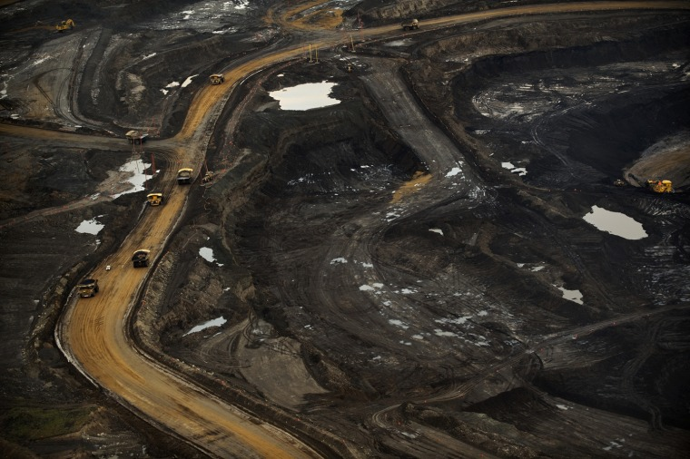 Aerial view of an oil sands mine north of Fort McMurray.   The Oil Sands or Tar Sands region in Alberta, Canada is now one of the largest producers of petroleum in the world. The Athabasca Oil Sands (also known colloquially as the Athabasca Tar Sands although there is no actual tar) are large deposits of bitumen, or extremely heavy crude oil, located in northeastern Alberta, Canada - roughly centered around the boomtown of Fort McMurray. These oil sands, hosted in the McMurray Formation, consist of a mixture of crude bitumen (a semi-solid form of crude oil), silica sand, clay minerals, and water. The Athabasca deposit is the largest reservoir of crude bitumen in the world and the largest of three major oil sands deposits in Alberta, along with the nearby Peace River and Cold Lake deposits. Together, these oil sand deposits lie under 141,000 square kilometres (54,000 sq mi) of sparsely populated boreal forest and muskeg (peat bogs) and contain about 1.7 trillion barrels (270?10^9 m3) of bitumen in-place, comparable in magnitude to the world's total proven reserves of conventional petroleum.  With modern unconventional oil production technology, at least 10% of these deposits, or about 170 billion barrels (27?10^9 m3) were considered to be economically recoverable at 2006 prices, making Canada's total oil reserves the second largest in the world, after Saudi Arabia's. The Athabasca deposit is the only large oil sands reservoir in the world which is suitable for large-scale surface mining, although most of it can only be produced using more recently developed in-situ technology.[