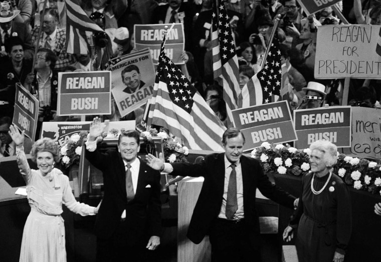 Republican presidential candidate Ronald Reagan and his running mate George Bush are shown on the podium of Joe Louis Arena in Detroit, July 17, 1980 as the final curtain draws near on the 1980 Republican National Convention. Nancy Reagan stands left, Barbara Bush, right. (AP Photo)