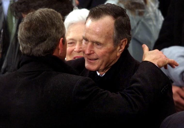 US President George W. Bush (L) is hugged by his f