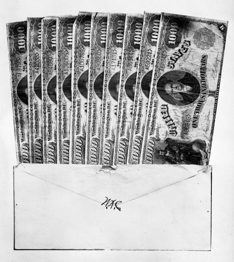 "Thousand dollar bills in an envelope bearing the initials ""W.A.C.,"" supposedly used to bribe Montana legislators to send William Andrews Clark to the U.S. Senate in 1899. Not for re-use without permission of the Montana Historical Society."