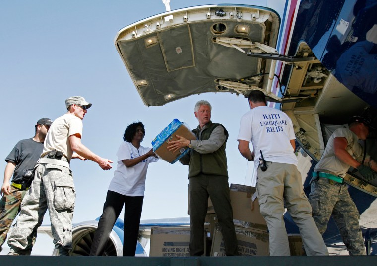 Image: Former U.S. President Bill Clinton helps unload a cargo plane at Port-au-Prince airport in Haiti