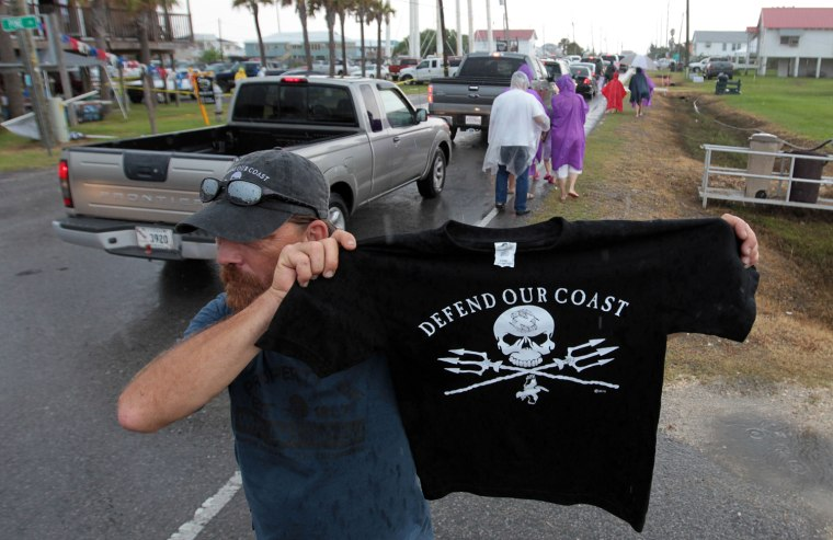 Image: James Wilson sells T-shirts to those arriving in Grand Isle, La., for Island Aid 2010