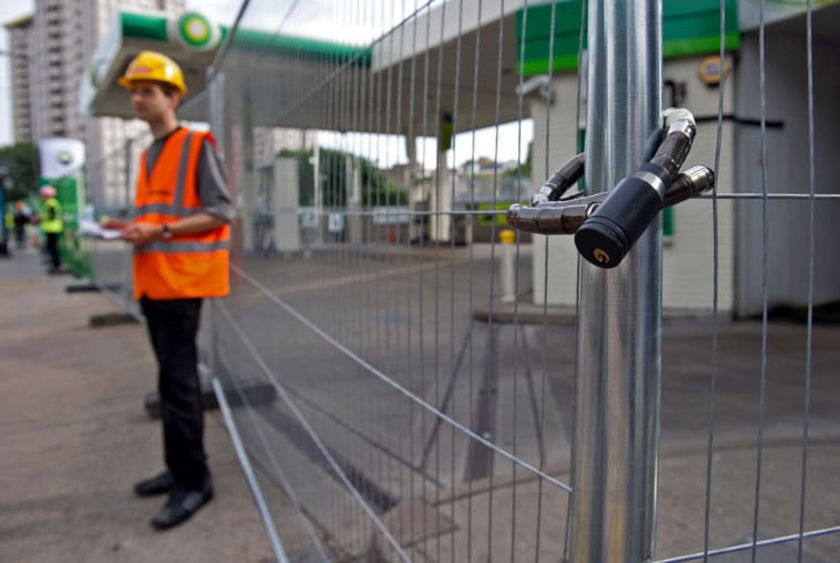 Image: Demonstrators stand outside a BP petrol station, which they have barricaded with fences, in London
