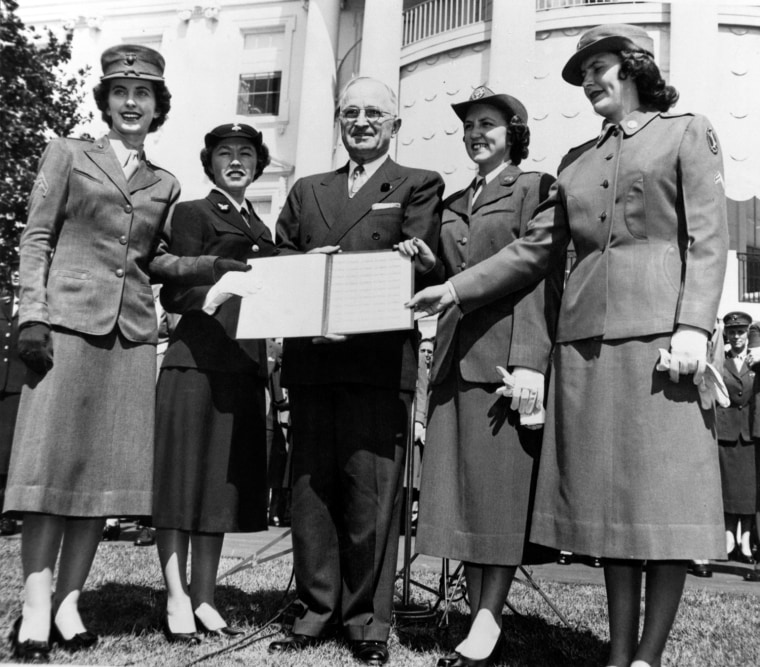 """President Harry S. Truman is joined by a representatives of the Marine Corps, Navy, Air Force and Women's Army Corps at a ceremony at the White House celebrating the first day of sale of the new stamp """"Women in our Armed Services"""", 11 September 1952.  National Archives (111-SC-400576)  President Harry S. Truman was presented booklets containing first issues of the new three-cent stamp honoring women of the services....Representing the women's services with President Truman (center) are left to right: Corporal Frances Klein, USMC; Seaman Thelma Bunty, USN; Airman First Class Alta Parker, USAF; and Corporal Lorraine Schwanker?, WAC.  Washington, DC, 11 September 1952.  National Archives (111-SC-400576)"""