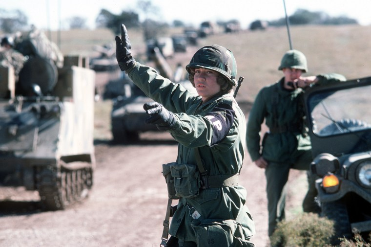 A U.S. Army military policewoman directs convoy of armored vehicles. A U.S. Army military policewoman directs convoy of armored vehicles, December 1978.  Defense Visual Information Center