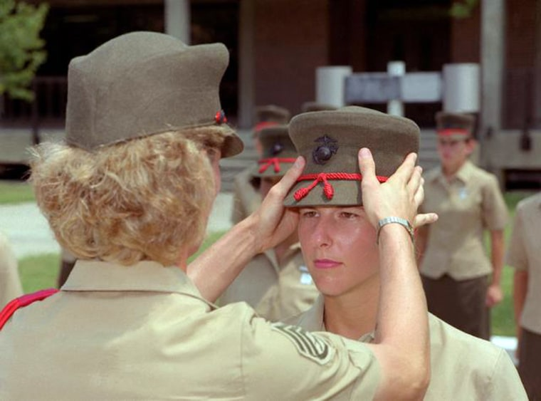 A drill instructor replaces a 4th Battalion recruit's cover after attaching the Marine Corps emblem during the emblem ceremony. The 4th Battalion is the only all female unit in the Marine Corps. Location: USMC RECRUIT DEPOT,PARRIS ISLAND, SOUTH CAROLINA (SC) UNITED STATES OF AMERICA (USA) Camera Operator: LCPL DRAKE Date Shot: 23 Jul 1991 Defense Visual Information Center