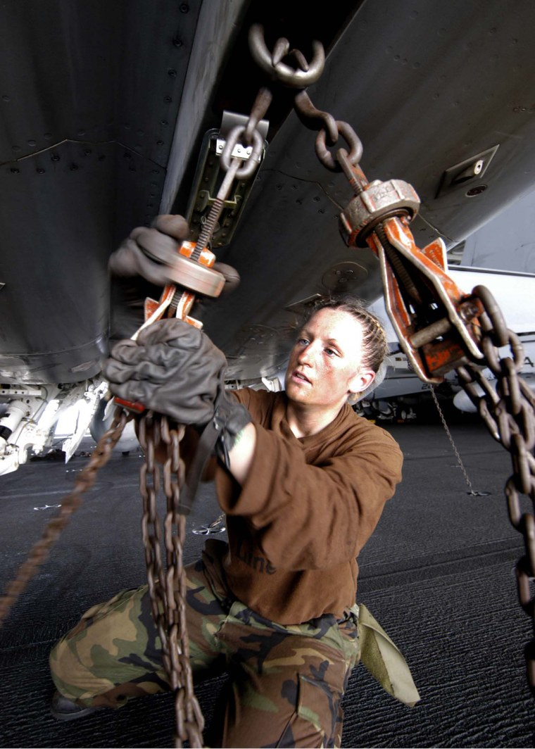050204-N-0499M-024 Airman Jolenea Pederson tightens a tie-down chain on an F/A-18E Hornet aboard the aircraft carrier USS Abraham Lincoln (CVN 72) on Feb. 3, 2005.  The Lincoln Strike Group is operating in the Indian Ocean in the waters off the coast of Indonesia in support of Operation Unified Assistance.  The Hornet is assigned to Strike Fighter Squadron 137.  DoD photo by Petty Officer 3rd Class James R. McGury, U.S. Navy.  (Released)