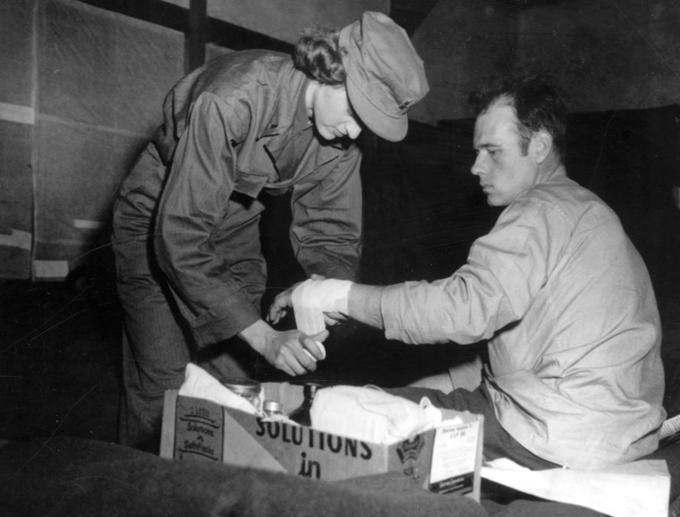 An Army nurse bandages the wrist of a wounded soldier, Korea, 11 February 1951.  National Archives (111-SC-358221)