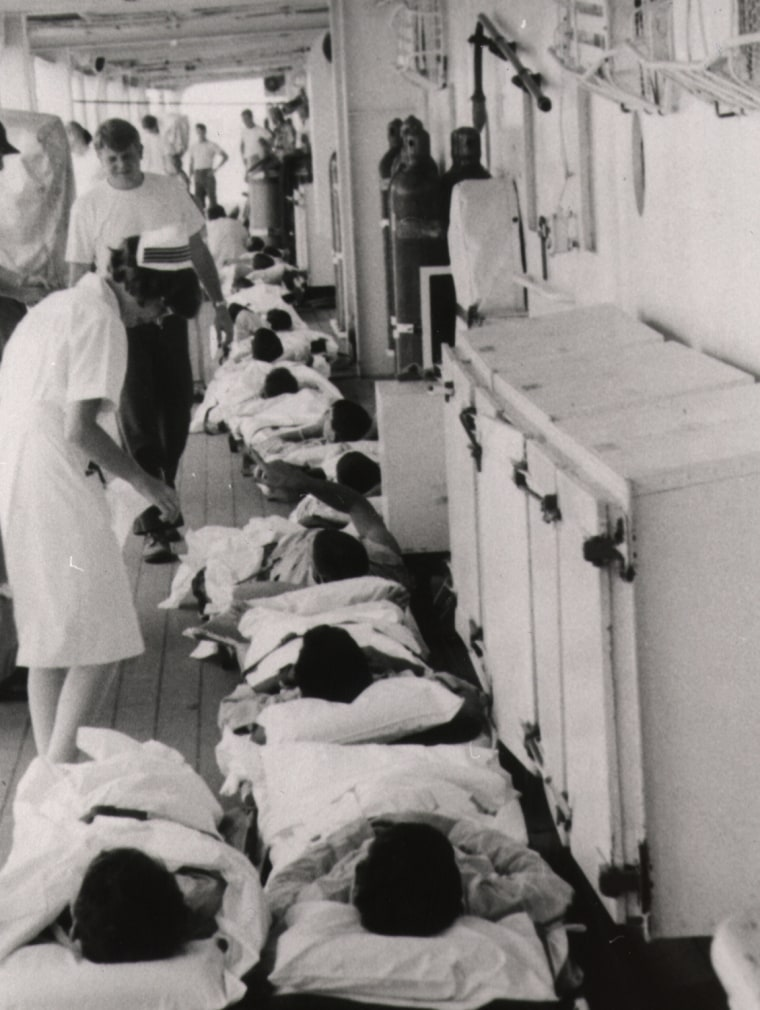A Navy nurse attends the sick and wounded on stretchers on the deck of the hospital ship USS Sanctuary (AH-17) moored in Da Nang Harbor.  The men have just arrived aboard by a medical evacuation helicopter. April 1970.  National Archives (428-GX-20004)