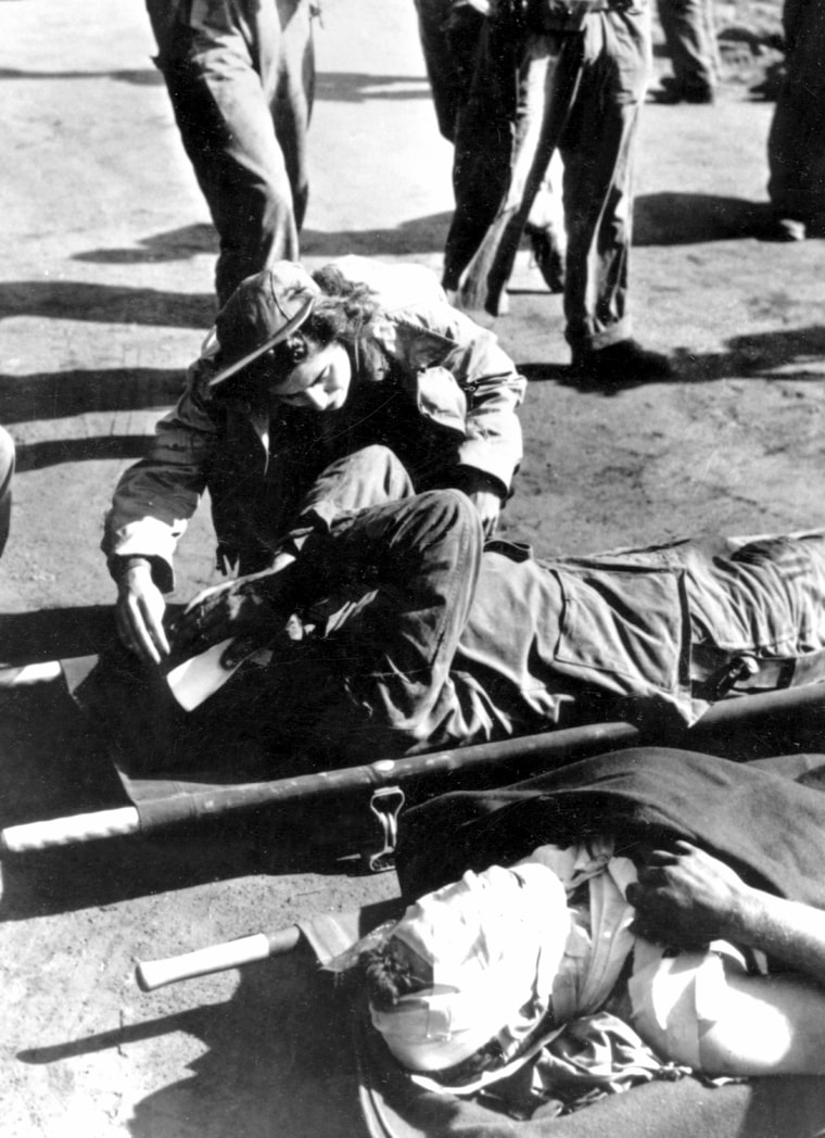 Navy nurse Ensign Jane Kendeigh, USNR, first navy flight nurse to reach Iwo Jima, ministers to serious casualties awaiting evacuation on the air strip, March 1945.  US Naval Historical Center (NH 95014)