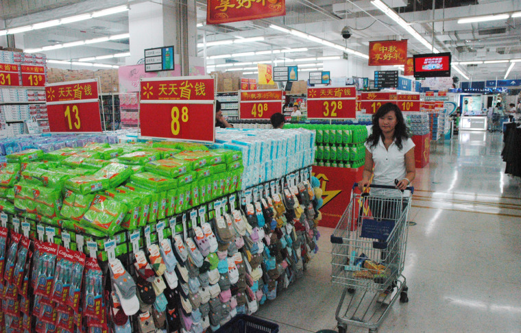 A shopper walks past a familiar-looking displayat a Wal-Mart store in Beijing. China's red-hot economy has raised the living standards of urban households. But hundreds of millions of rural workers earn about $2 a day.