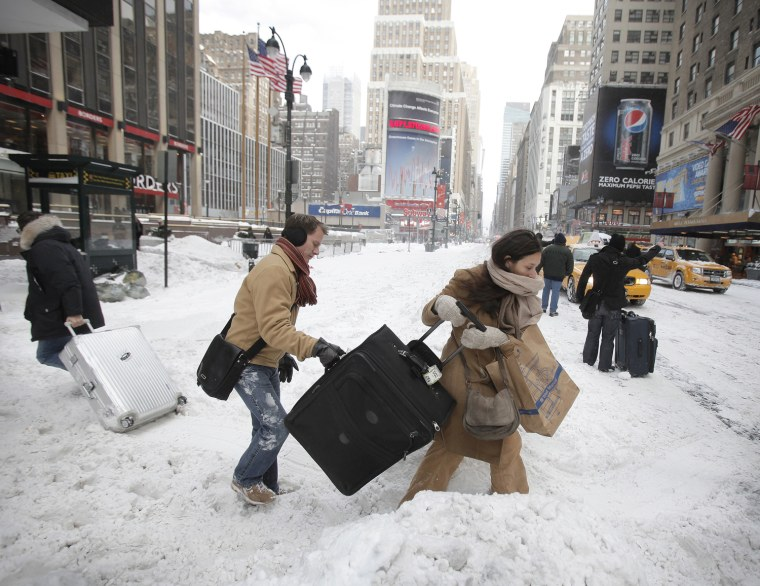 Image: Travellers carry their luggage through a snow bank on 7th Avenue in front of Penn Station after a snow storm in New York