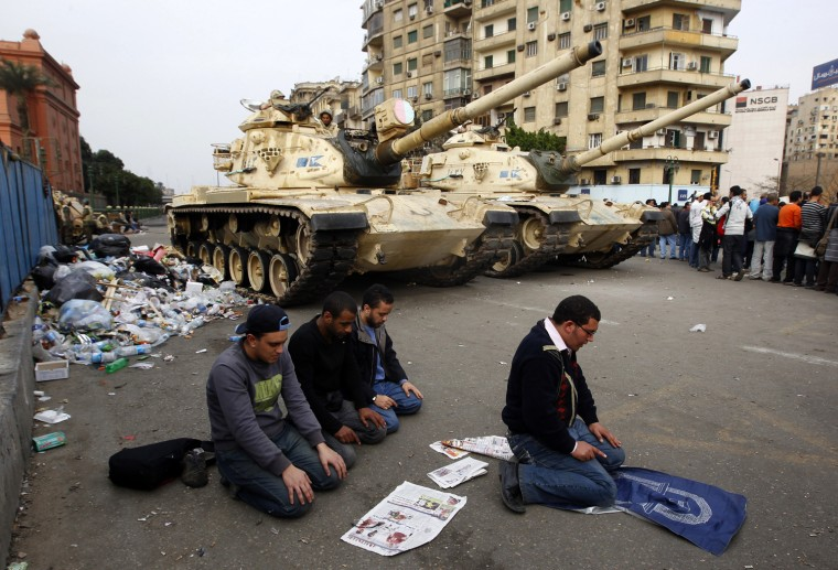 Image: Protesters pray in front of Army tanks during a mass demonstration against the government in Tahrir Square in Cairo