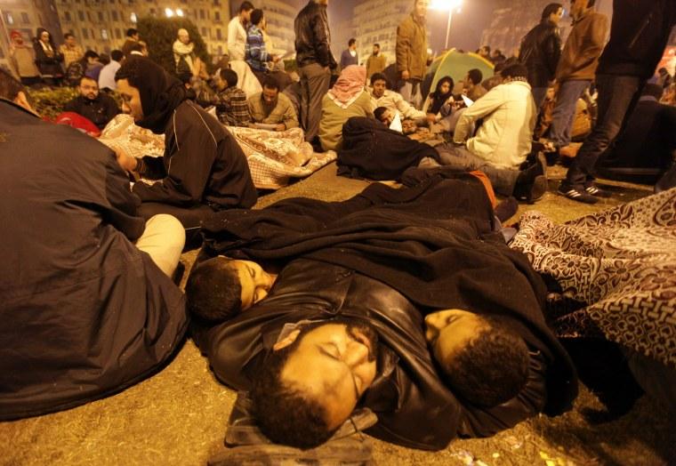 Image: An Egyptian demonstrator sleeps with his