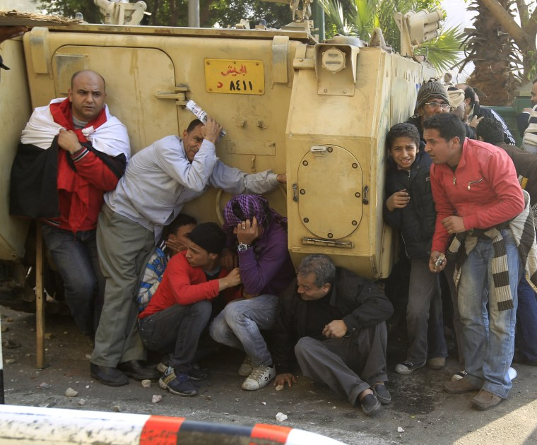 Image: Demonstrators take cover during rioting between pro and anti Mubarak supporters in Tahrir Square in Cairo