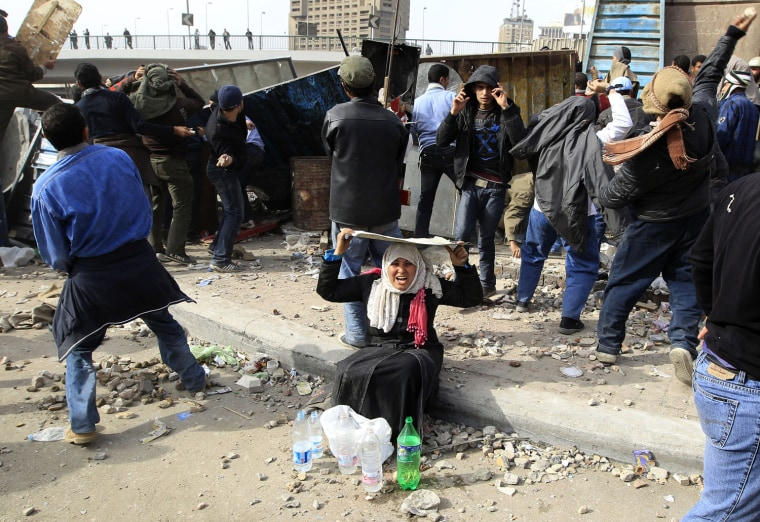 Image: A woman opposition supporter takes shelter while providing water during rioting with pro-Mubarak demonstrators near Tahrir Square in Cairo