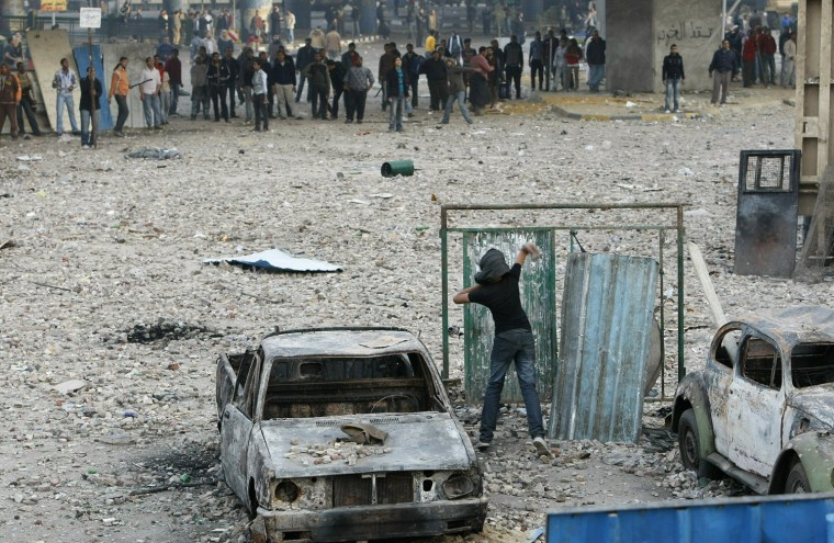 Image: An Egyptian anti-government demonstrator throws a projectile at pro-regime opponents
