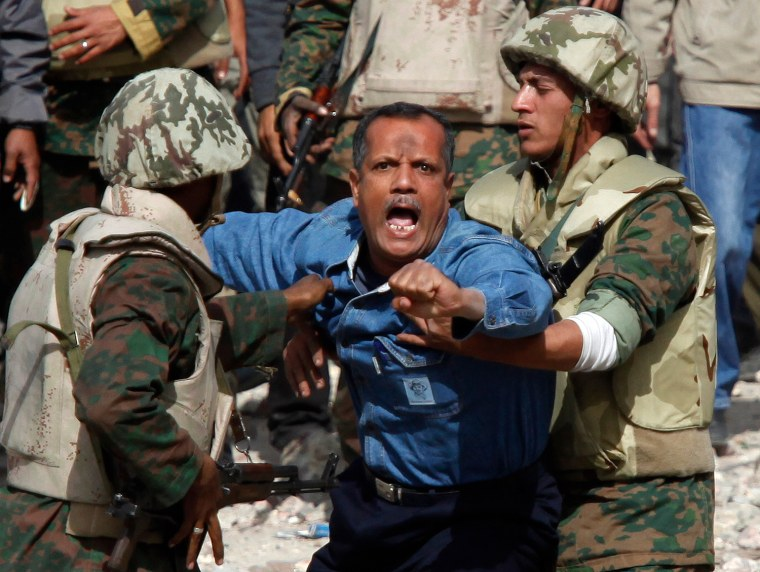 Image: Egyptian soldiers restrain a supporter of Mubarak who tried to get to opposition lines near Tahrir Square in Cairo