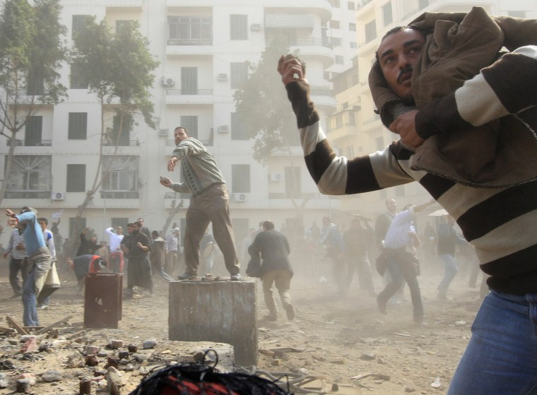 Image: Opposition supporters throw stones at pro-Mubarak demonstrators in Tahrir Square in Cairo