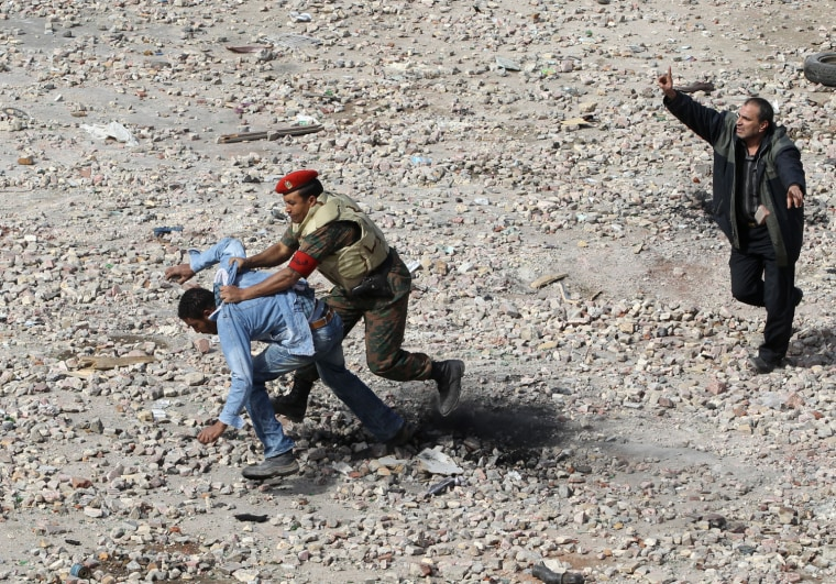 Image: Supporter of Egyptian President Hosni Mubarak is taken to the ground by a soldier in Cairo