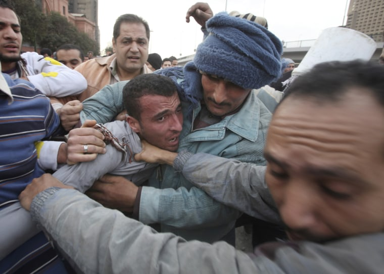 Image: A pro-Mubarak supporter apprehended by opposition demonstrators is led away during rioting near Tahir Square in Cairo