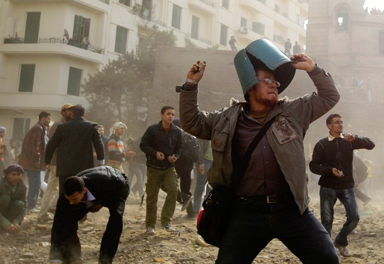 Image: An opposition demonstrator throws a rock during rioting with pro-Mubarak supporters near Tahrir Square in Cairo