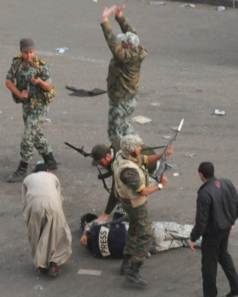 Image: A member of the press lies on the ground after being attacked by mobs while soldiers surround him in Cairo