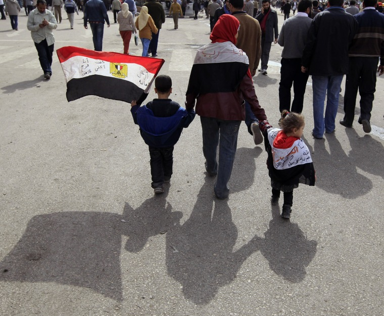 Image: An opposition supporter walks with children to Friday prayers in Tahrir Square in Cairo