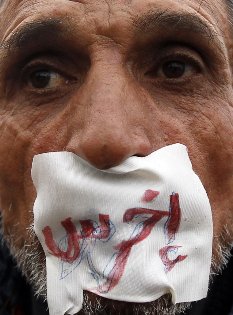 """Image: An anti-government demonstrator looks on with a sign reading """"shut up"""" over his mouth near Tahrir Square in Cairo"""
