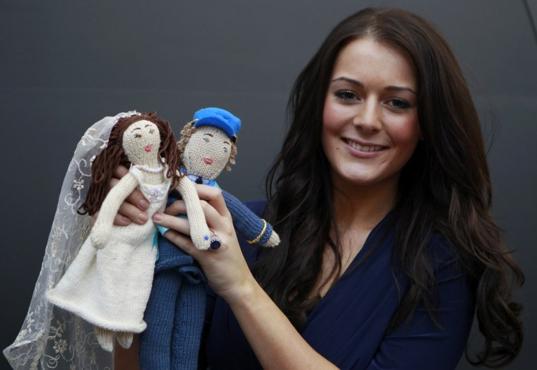 Image: Kate Bevan, a lookalike of Kate Middleton, the fiancee of Britain's Prince William, poses for a photograph with a knitted toy inspired by the forthcoming royal wedding, at a toy fair in London