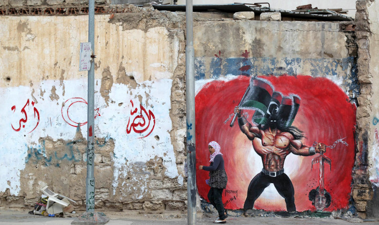 Topshots A Libyan Girl Walks Past Pro Revolution Graffiti In Tripoli On October   Forces Of Libyas New Regime Were Looking To Move In For The Kill